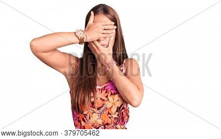 Young beautiful hispanic woman wearing casual clothes covering eyes and mouth with hands, surprised and shocked. hiding emotion