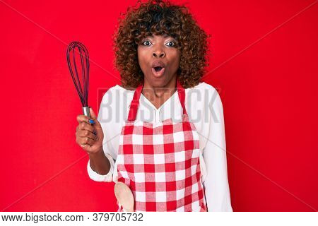 Young african american woman wearing apron holding whisk scared and amazed with open mouth for surprise, disbelief face