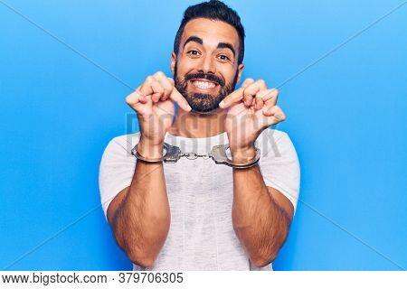 Young hispanic man wearing prisoner handcuffs smiling happy pointing with hand and finger