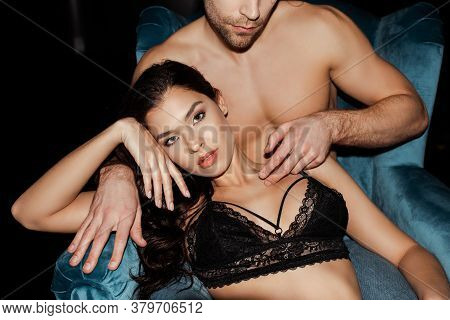 Muscular Man Touching Neck Of Attractive Woman In Bra On Armchair On Black