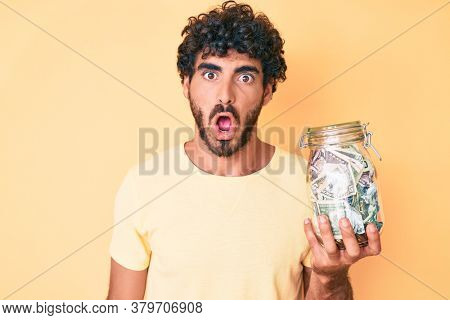 Handsome young man with curly hair and bear holding jar with savings scared and amazed with open mouth for surprise, disbelief face