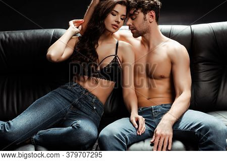 Beautiful Brunette Woman In Bra And Jeans Sitting Beside Shirtless Boyfriend On Black