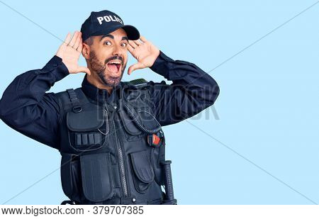 Young hispanic man wearing police uniform smiling cheerful playing peek a boo with hands showing face. surprised and exited