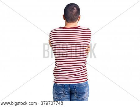 Young handsome man wearing striped sweater hugging oneself happy and positive from backwards. self love and self care