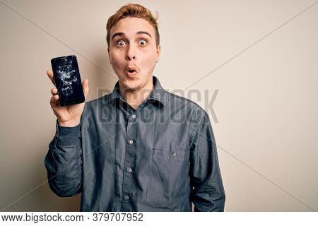 Young handsome redhead man holding broken smartphone showing cracked screen scared and amazed with open mouth for surprise, disbelief face