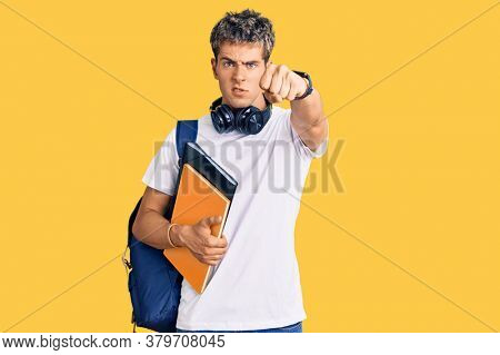 Young handsome man holding student backpack and books annoyed and frustrated shouting with anger, yelling crazy with anger and hand raised