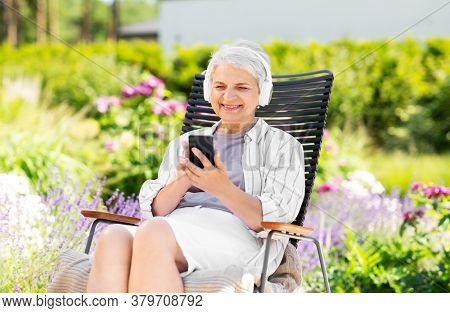 old age, retirement and people concept - happy senior woman with headphones and smartphone listening to music at summer garden