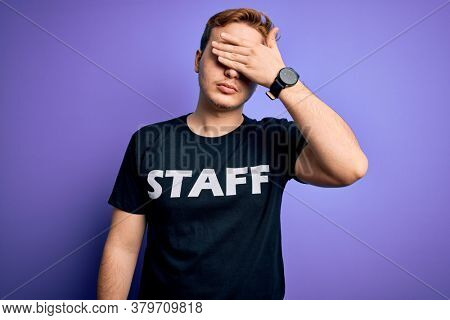 Young handsome redhead worker man wearing staff t-shirt uniform over purple background covering eyes with hand, looking serious and sad. Sightless, hiding and rejection concept