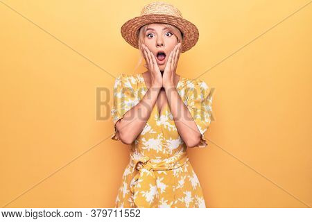Beautiful blonde woman on vacation wearing summer hat and dress over yellow background afraid and shocked, surprise and amazed expression with hands on face