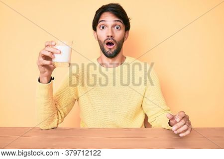 Handsome hispanic man holding glass of milk scared and amazed with open mouth for surprise, disbelief face
