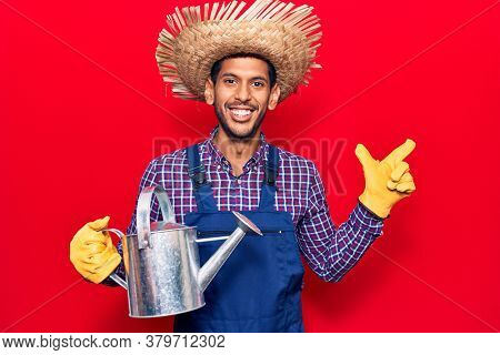 Young latin man wearing farmer hat and gloves holding watering can smiling happy pointing with hand and finger to the side