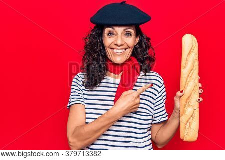 Middle age beautiful woman wearing french beret holding baguette smiling happy pointing with hand and finger