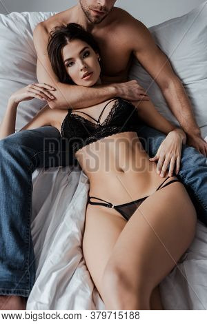 Man Embracing Sensual Brunette Girlfriend On Bed