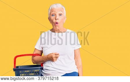 Senior beautiful woman with blue eyes and grey hair holding supermarket shopping basket scared and amazed with open mouth for surprise, disbelief face