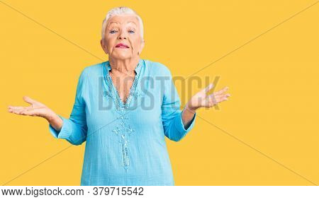 Senior beautiful woman with blue eyes and grey hair wearing summer dress clueless and confused expression with arms and hands raised. doubt concept.