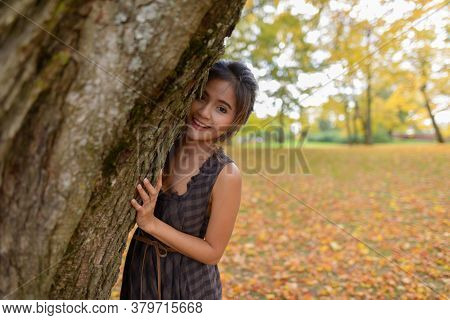 Young Happy Asian Woman Smiling While Playfully Hiding Behind Tree