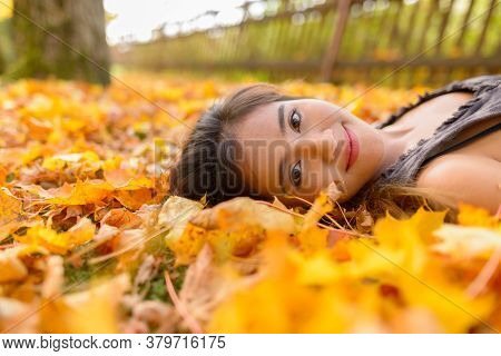 Young Beautiful Asian Woman Lying Down On Yellow Autumn Leaves