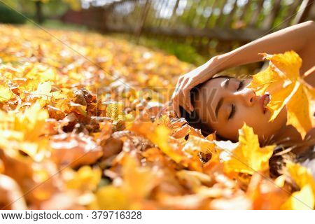 Young Beautiful Asian Woman Lying Down With Eyes Closed On Yellow Autumn Leaves