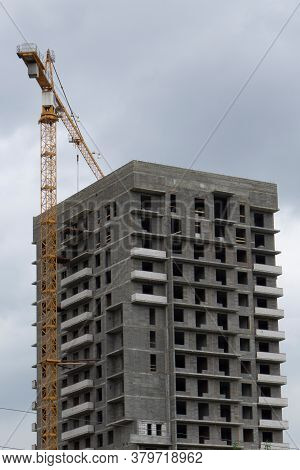 Unfinished Multi-storey Building. Construction Crane On A Background Of Gloomy Sky.