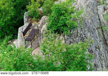 Lonely Bench In The Mountains, Top View. Secluded Bench On The Stones Among The Greenery.