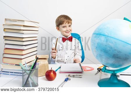 Preschool Education: A Little Boy In A Shirt And A Red Bow Tie Smiles, Sits At A Desk And Holds A Pe