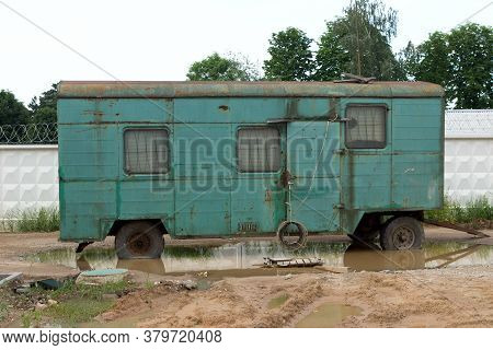 Old Green Rusty Construction Camper, Trailer, Van Or Wagon. Construction Site In The City.