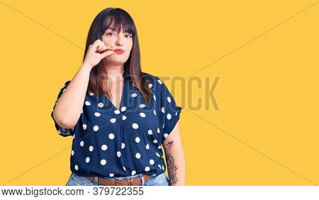 Young plus size woman wearing casual clothes mouth and lips shut as zip with fingers. secret and silent, taboo talking