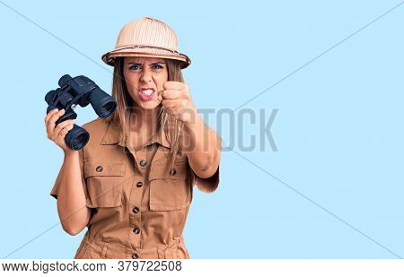 Young beautiful woman wearing explorer hat holding binoculars annoyed and frustrated shouting with anger, yelling crazy with anger and hand raised