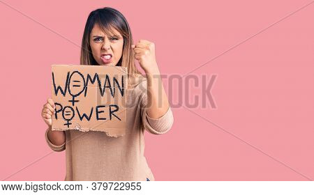 Young beautiful woman holding woman power banner annoyed and frustrated shouting with anger, yelling crazy with anger and hand raised