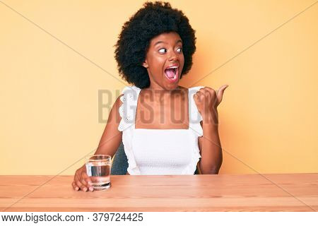 Young african american woman drinking glass of water pointing thumb up to the side smiling happy with open mouth