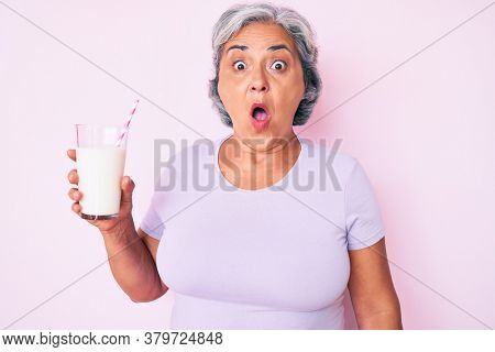 Senior hispanic woman holding glass of milk scared and amazed with open mouth for surprise, disbelief face