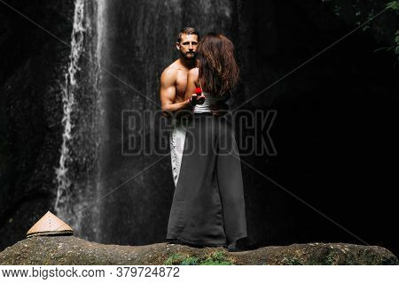 Offer Of A Hand In Travel. Honeymoon Trip. A Man Proposes To A Woman At A Waterfall. A Guy Proposes