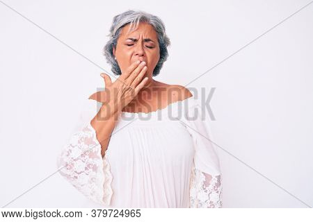 Senior hispanic grey- haired woman wearing casual clothes bored yawning tired covering mouth with hand. restless and sleepiness.