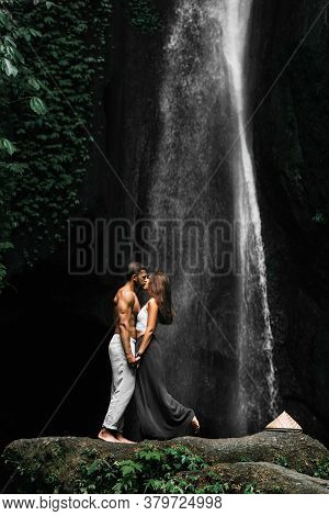 Beautiful Couple At A Waterfall In Indonesia. A Couple In Love Travels Around The Island Of Bali. A