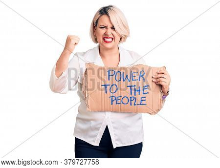 Young blonde plus size woman holding power to the people banner annoyed and frustrated shouting with anger, yelling crazy with anger and hand raised