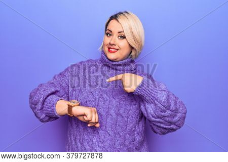 Beautiful blonde plus size woman wearing casual turtleneck sweater over purple background In hurry pointing to watch time, impatience, upset and angry for deadline delay