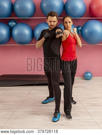 Image Of A Young Couple Doing Exercises In A Gym