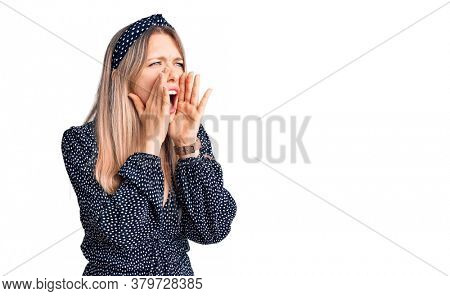 Young beautiful blonde woman wearing casual clothes shouting angry out loud with hands over mouth