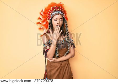 Young beautiful latin girl wearing indian costume bored yawning tired covering mouth with hand. restless and sleepiness.