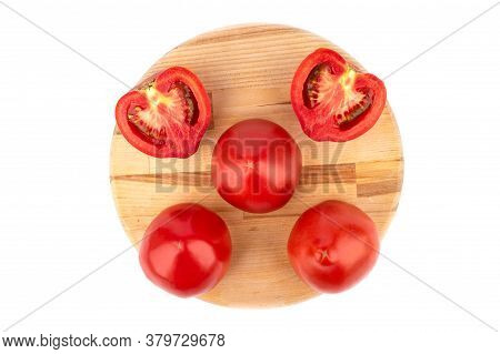 Flat Lay. Ripe Tomatoes And Tomato Halves On A Wooden Cutting Board. Ripe Tomatoes Over A White Back