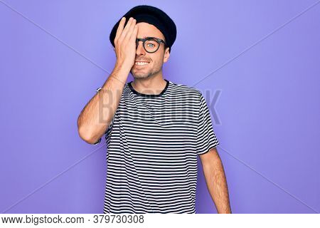 Handsome man with blue eyes wearing striped t-shirt and french beret over purple background covering one eye with hand, confident smile on face and surprise emotion.