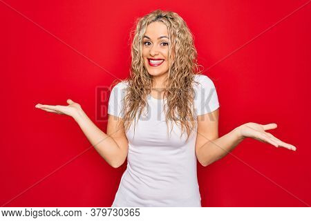 Young beautiful blonde woman wearing casual t-shirt standing over isolated red background clueless and confused expression with arms and hands raised. Doubt concept.