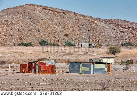 Traditional African Hut From Rusty Sheet Of Tin In Desert Of Erongo Region. In Background Is Brandbe