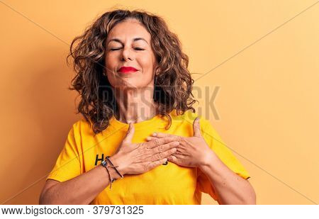 Middle age beautiful woman wearing t-shirt with happiness word over yellow background smiling with hands on chest, eyes closed with grateful gesture on face. Health concept.