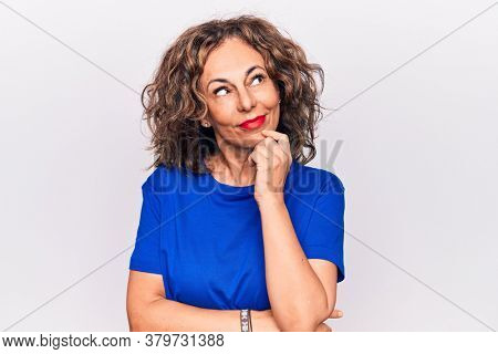 Middle age beautiful brunette woman wearing blue t-shirt standing over white background thinking concentrated about doubt with finger on chin and looking up wondering