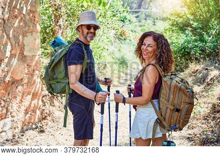 Beautiful couple of hiker wearing backpack smiling happy. Standing with smile on face doing trekking using hiking stick at forest