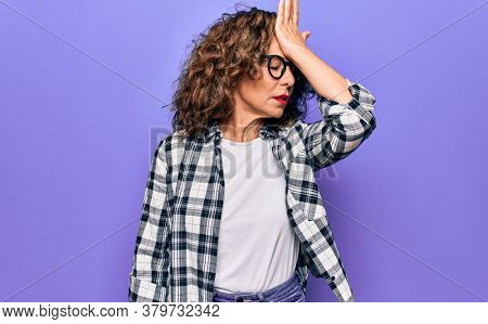 Middle age beautiful woman wearing casual shirt and glasses over isolated purple background surprised with hand on head for mistake, remember error. Forgot, bad memory concept.