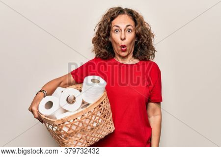 Middle age woman holding wicker basket with lots of toilet paper rolls over white background scared and amazed with open mouth for surprise, disbelief face