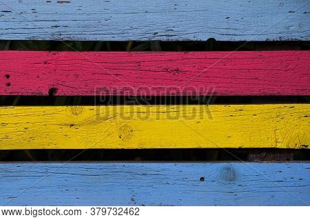 Front View Closeup Of Horizontal Wood Timber Planks Colored In Red Yellow And Light Blue