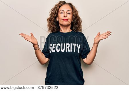 Middle age beautiful guard woman wearing security t-shirt uniform over white background clueless and confused with open arms, no idea and doubtful face.